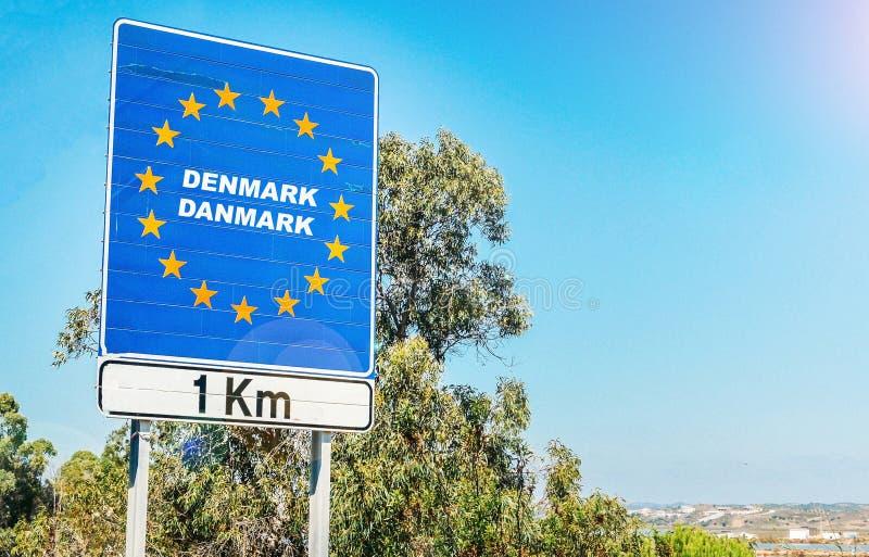 Verkehrsschild auf der Grenze eines Landes der Europäischen Gemeinschaft, Dänemark 1km voran mit Kopienraum des blauen Himmels lizenzfreie stockfotos