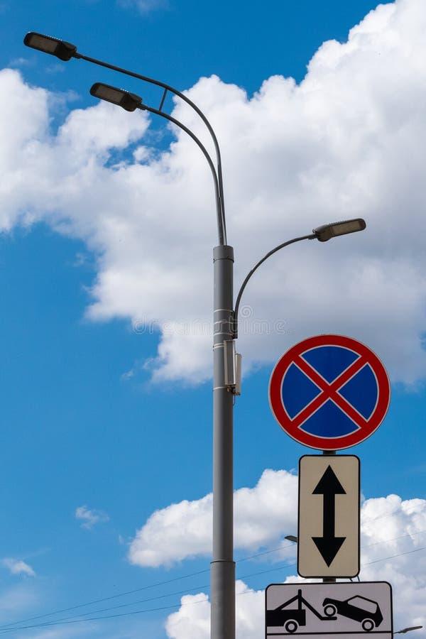 Verkehrsschilder gegen den blauen Himmel, die flaumigen Wolken und eine Straßenlaterne Zeichen-Halt wird und Evakuierung des Auto lizenzfreie stockfotos