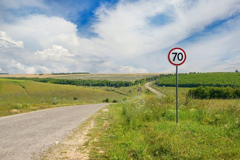 Verkehrsschildgrenzgeschwindigkeit auf einer Landstraße lizenzfreies stockbild