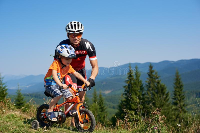 Verkhovyna, Ukraine - August 19, 2017: Father teaches preschool boy to ride a bike on grassy mountain hill royalty free stock images