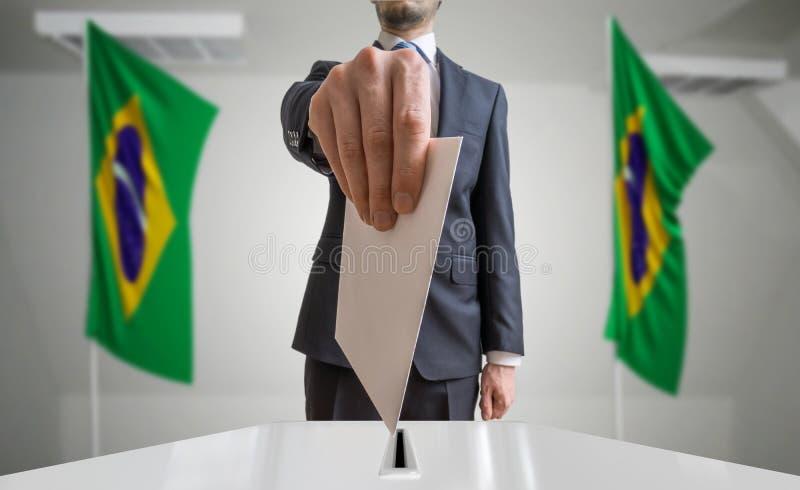 Verkiezing of referendum in Brazilië De kiezer houdt envelop boven stemming in hand Braziliaanse vlaggen op achtergrond royalty-vrije stock afbeelding