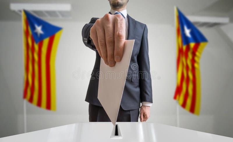Verkiezing of referendum in Catalonië De kiezer houdt envelop boven stemming in hand Catalaanse vlaggen op achtergrond stock fotografie
