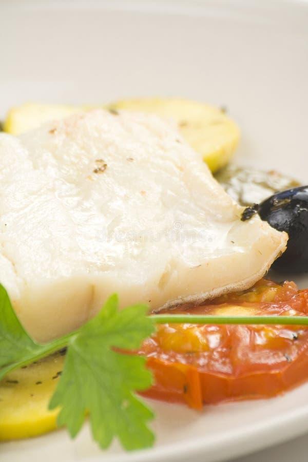 Verkleidung des Kabeljaus backte schwarze Oliven der Tomatezucchini lizenzfreies stockbild