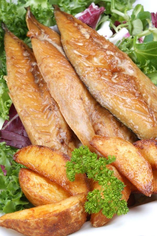 Verkleidungen der geräucherten Makrele mit gegrillten Kartoffelkeilen stockbild
