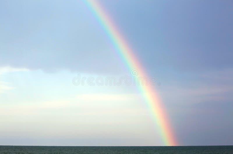 Verklig regnbåge efter stormen över havet och den blåa himlen royaltyfri bild