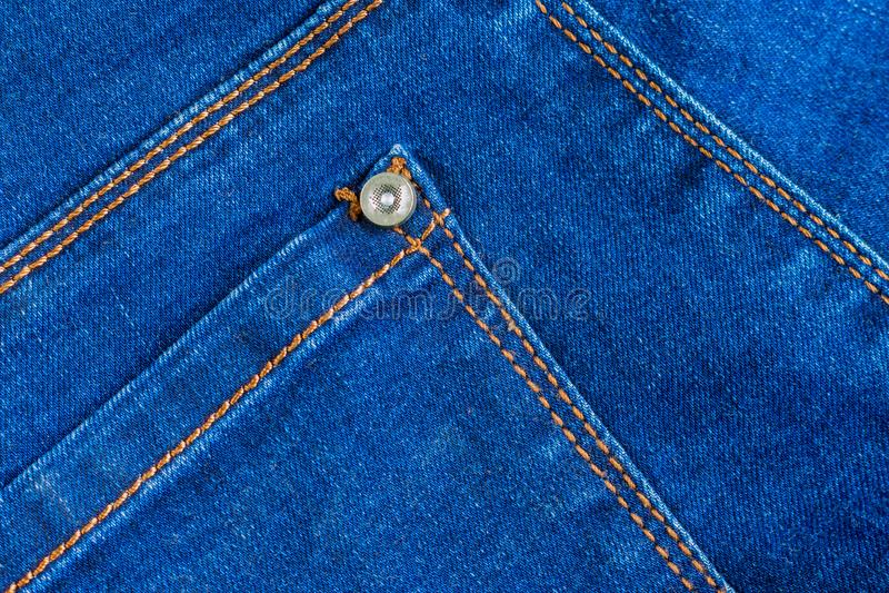 Verklig textur för bakgrund för jeansgrov bomullstvilltyg tom bakficka med gult orange sy och niten royaltyfria foton