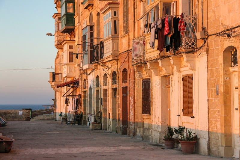 Verkliga livet på den Valletta gatan under orange solnedgång - ingen på trottoaren och kläder som torkar på typisk maltese balkon royaltyfria foton