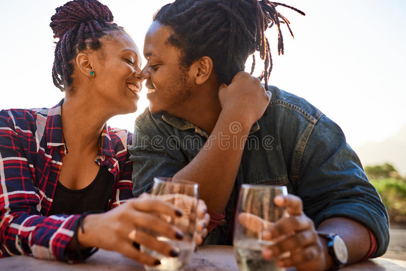 Verkliga par av den afrikanska nedstigningen omkring som ska kyssas, medan omfamna royaltyfri bild