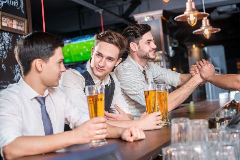 Verkliga vänner för möte Fyra vänmän som dricker öl och har gyckel arkivfoto