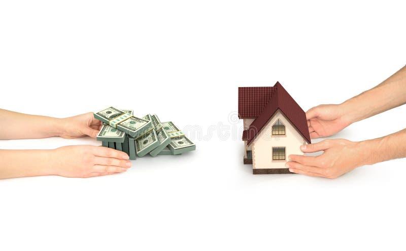 Verkligt astatebegrepp, hand med huset och händer med dollarräkningen arkivbild