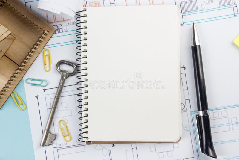verkligt begreppsgods Tom vit anteckningsbok på arkitektonisk bakgrund för skrivbordtabellritning med tangent, penna, litet hus royaltyfria foton