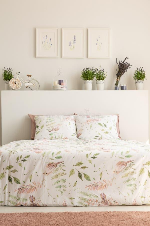 Verkligt foto av den blom- sovruminre med en dubbelsäng, kuddar arkivbilder