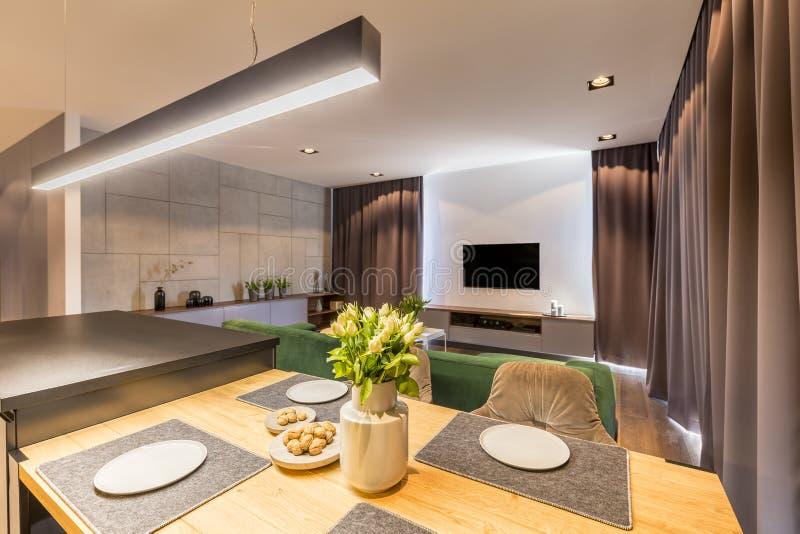 Verkligt foto av den trääta middag tabellen med plattor, nya tulpan i vas och muttrar i modern vardagsruminre med kök och dinin arkivbild