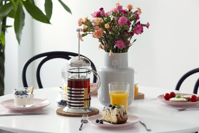 Verkligt foto av den vita äta middag tabellen med nya blommor i keramiskt v royaltyfria bilder