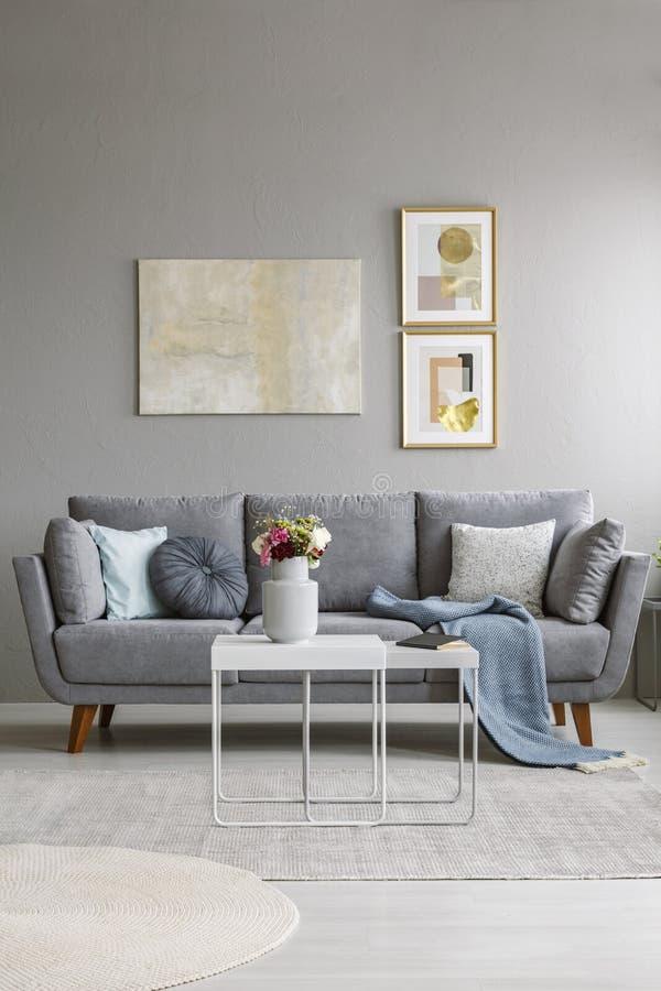 Verkligt foto av en grå soffa med kuddar och filtanseende in fotografering för bildbyråer