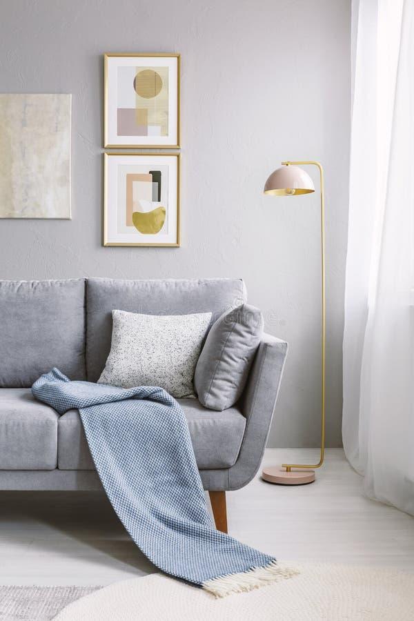 Verkligt foto av en grå soffa med kuddar och stående nex för filt royaltyfri foto