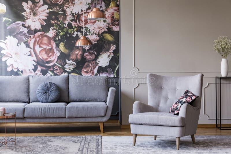Verkligt foto av en grå vardagsruminre med en soffa-, fåtölj-, tapet- och väggstöpning royaltyfri foto