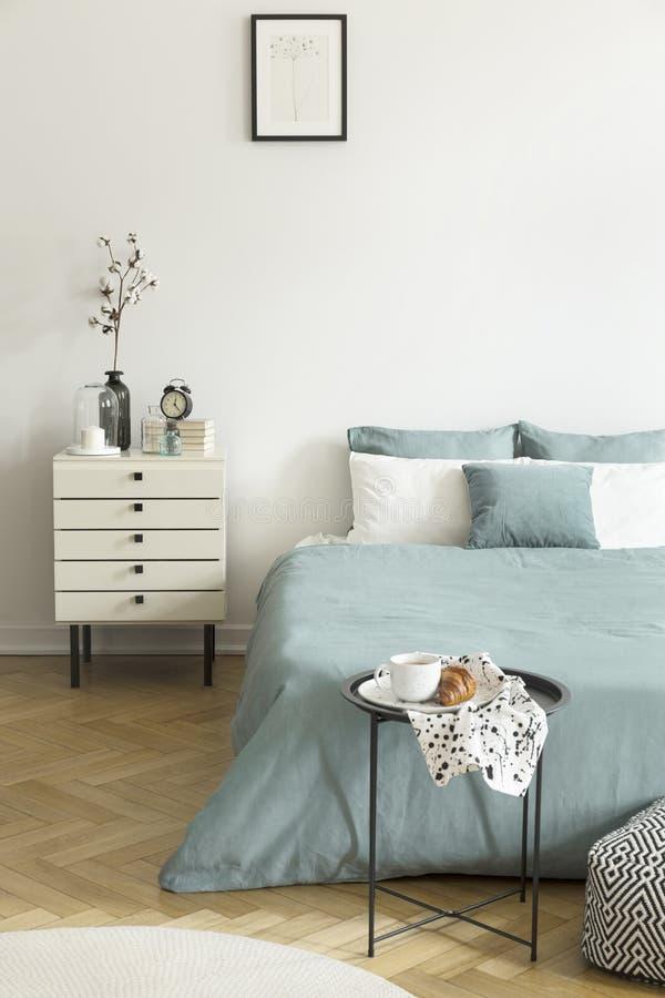 Verkligt foto av en inre för sovrum för kvinna` s med vita väggar, parkettgolvet, blek sängkläder för vis gräsplan och enhetskabi arkivbild