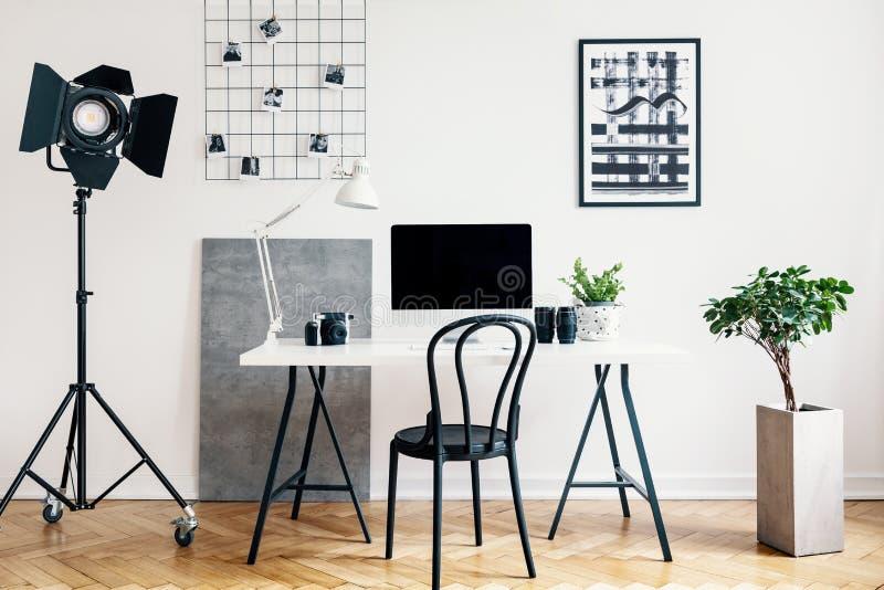 Verkligt foto av en inrikesdepartementetinre med en yrkesmässig lampa, skrivbord, stol, dator och växt Förlägga din logo på dator arkivfoto