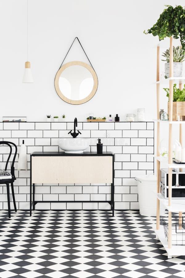 Verkligt foto av en modern badruminre med det rutiga golvet, spegeln, tvättställen med ett skåp och växter arkivfoto