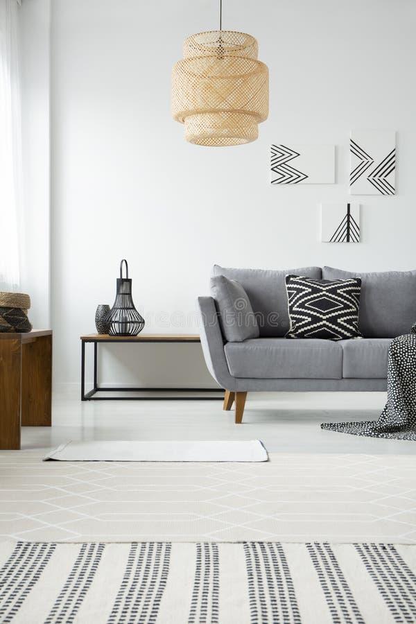 Verkligt foto av en rottinglampa som hänger ovanför en grå soffa med ett b arkivbilder