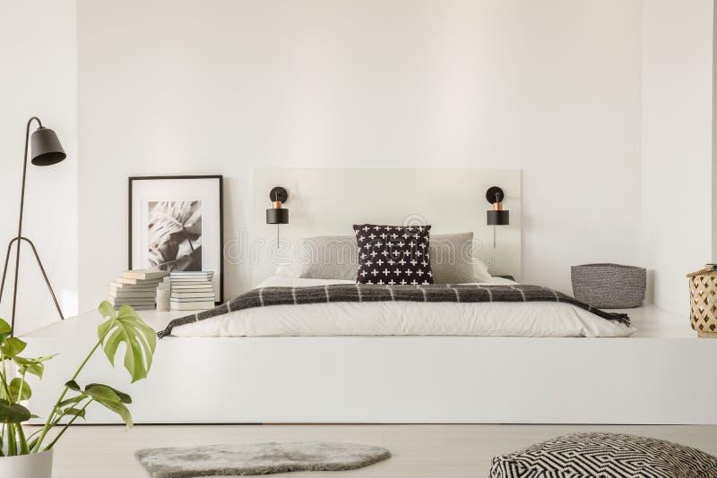 Verkligt foto av en säng med vitark, den svarta kudden och grå färgbla arkivfoto