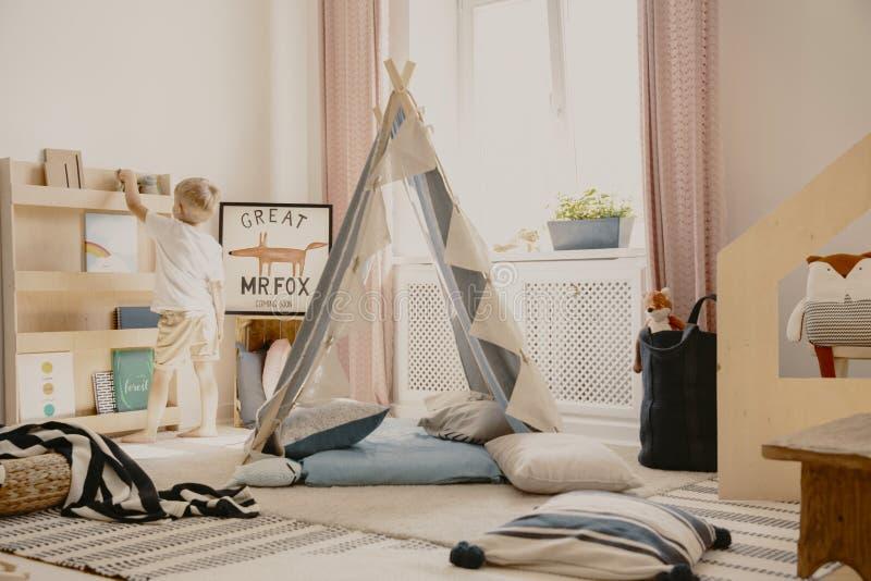 Verkligt foto av en scandilekruminre med ett tält och kuddar Pojke som sätter en leksak på en hylla arkivfoton