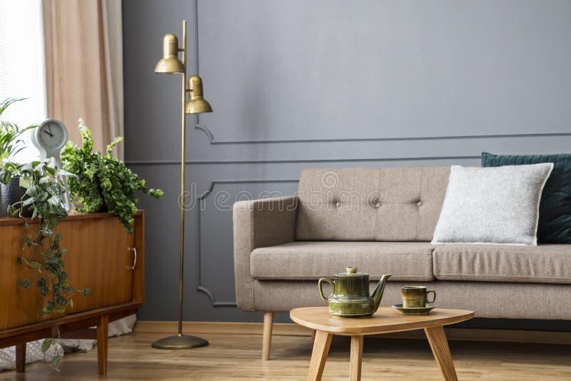 Verkligt foto av en soffa med kuddar som står bak en liten tabell arkivbild