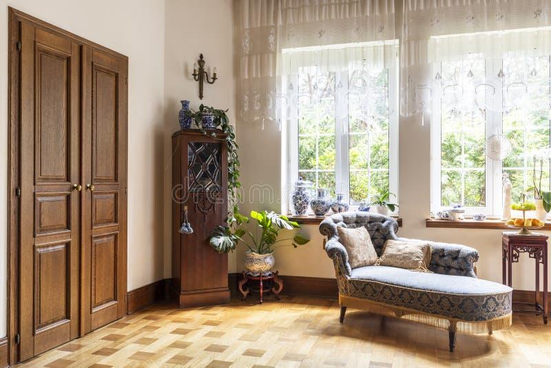 Verkligt foto av en vardagsruminre med en schäslong, porslinvaser, en trädörr och fönster med gardiner arkivbilder