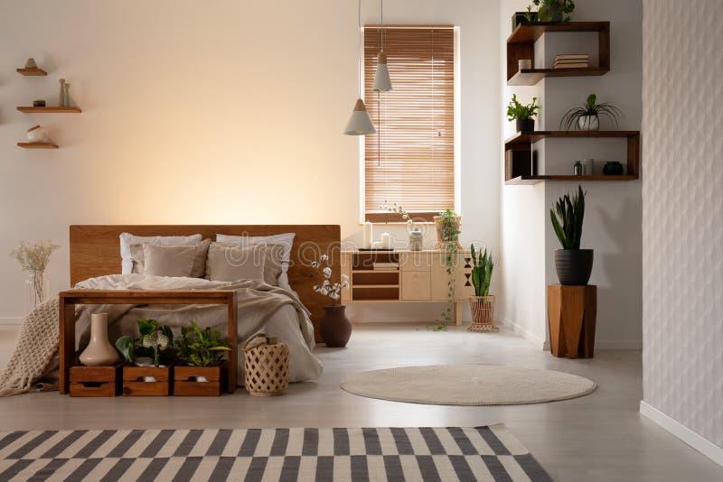 Verkligt foto av en varm sovruminre med träaskar och hyllor, dubbelsäng och växt Den tomma väggen, förlägger din logo arkivbild