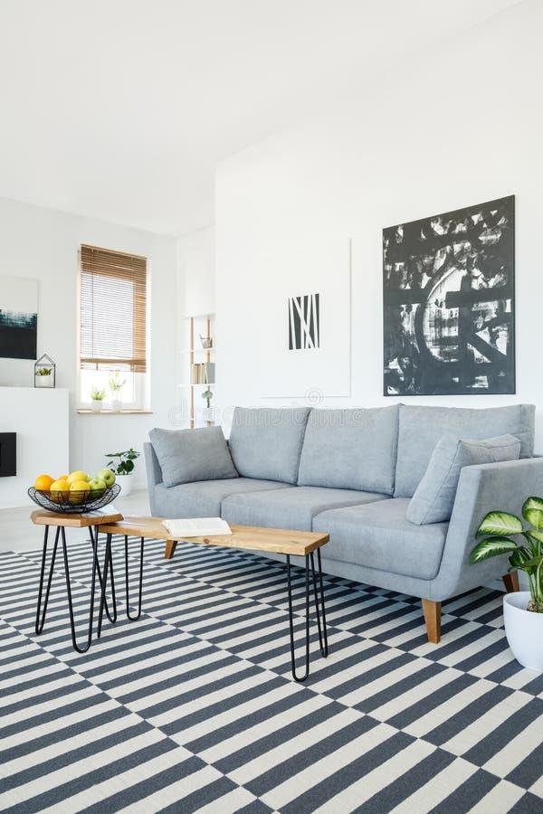 Verkligt foto av ett soffaanseende bredvid en vägg med vit och bla royaltyfri foto