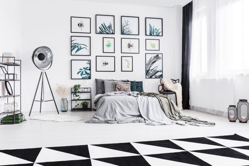 Verkligt foto av ett svartvitt sovrum med en stående betw för säng royaltyfria foton