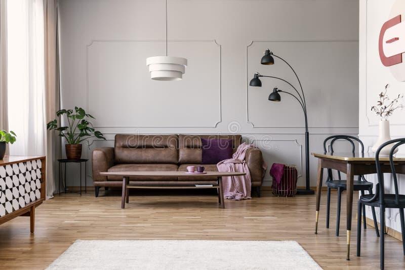 Verkligt foto av ljus - den gråa vardagsruminre med den bruna soffan med filten och violeten kudde, kaffetabellen med två tekoppa fotografering för bildbyråer