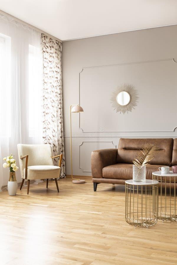 Verkligt foto av mycket av ljust dagligt rum med den retro fåtöljen, lampan, den bruna lädersoffan och tabeller royaltyfri fotografi