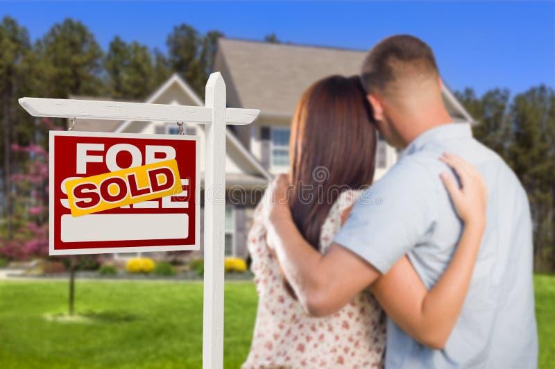 Verkocht voor Verkoopteken met Militair Paar die Huis bekijken stock fotografie