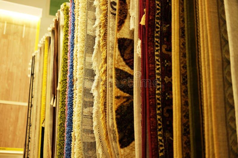 Verkoop Assortiment van verschillende tapijten in opslag close-upbeeld stock afbeelding