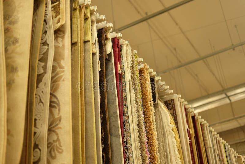 Verkoop - Assortiment van verschillende tapijten in opslag stock foto's