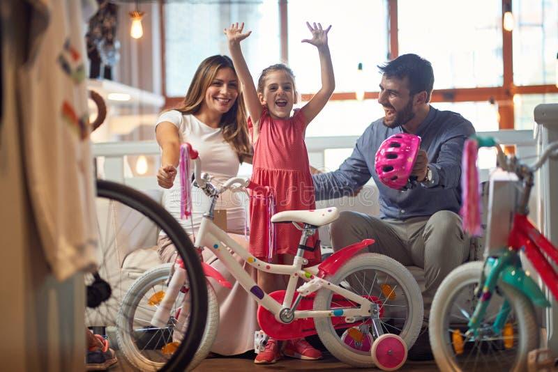Verkoop, consumentisme en mensenconcept - gelukkige familie met kind en het winkelen nieuwe fiets stock afbeelding