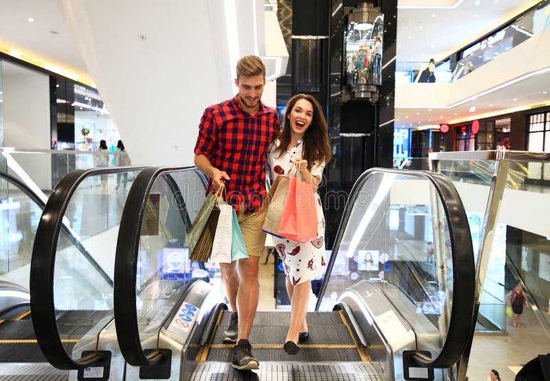 Verkoop, consumentisme en mensenconcept - het gelukkige jonge paar met het winkelen doet het lopen in wandelgalerij in zakken stock afbeeldingen