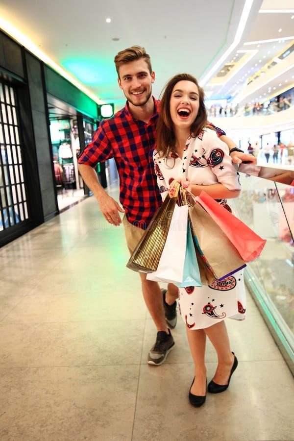 Verkoop, consumentisme en mensenconcept - het gelukkige jonge paar met het winkelen doet het lopen in wandelgalerij in zakken royalty-vrije stock foto's