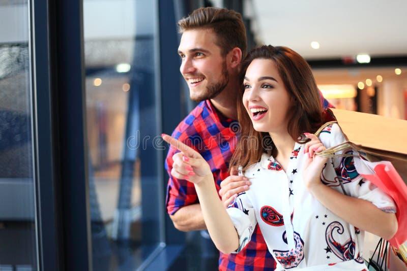 Verkoop, consumentisme en mensenconcept - het gelukkige jonge paar met het winkelen doet het lopen in wandelgalerij in zakken royalty-vrije stock fotografie