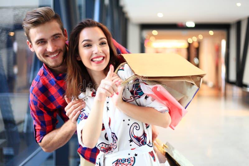 Verkoop, consumentisme en mensenconcept - het gelukkige jonge paar met het winkelen doet het lopen in wandelgalerij in zakken stock foto's