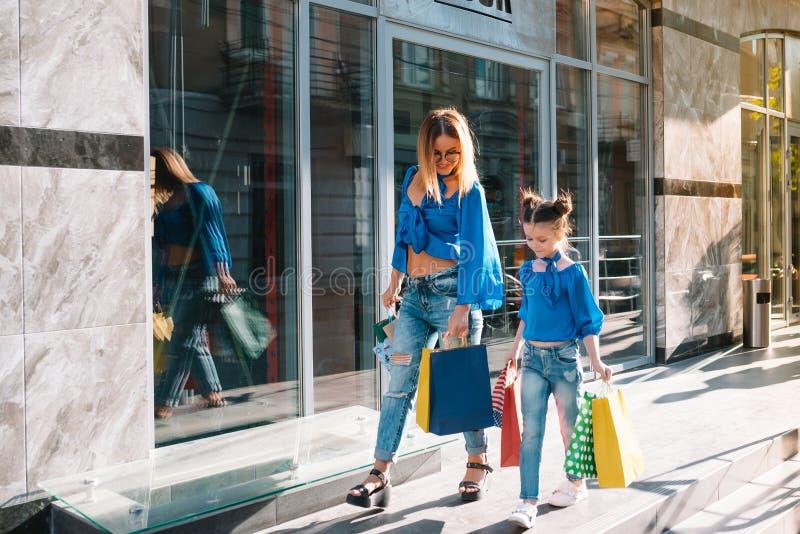 Verkoop consumentisme en mensensmokkel - gelukkige jonge vrouwen haar dochter met boodschappenzakken die de straat van de stad lo stock afbeeldingen
