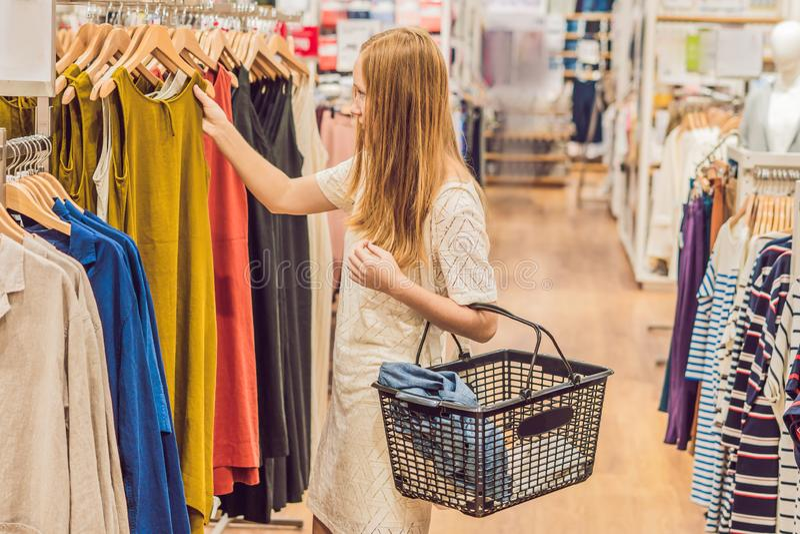 Verkoop, manier, consumentisme en mensenconcept - de gelukkige jonge vrouw met het winkelen doet het kiezen van kleren in wandelg stock foto