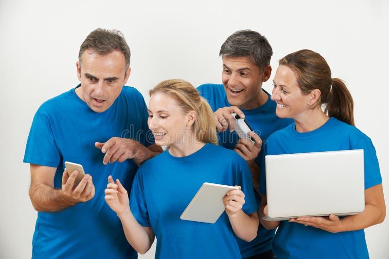 Verkoop Team Wearing Uniform With Selection van Techno-Gadgets stock afbeelding
