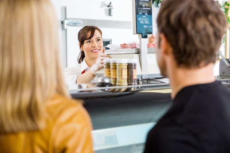 Verkoopster Looking At Customers in Slagerij stock foto's