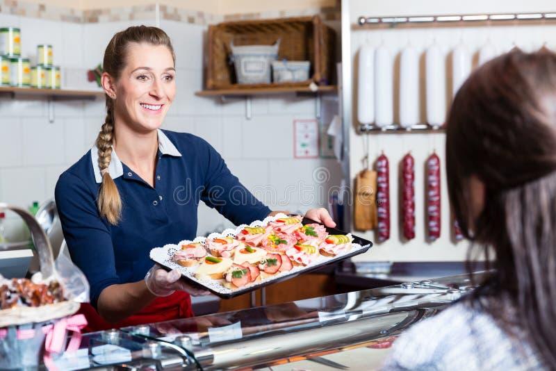 Verkoopvrouw in slagerij die vingervoedsel aanbieden royalty-vrije stock foto's
