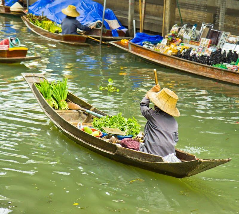 Verkopend voedsel op een boot bij het drijven markt, Thailand stock foto