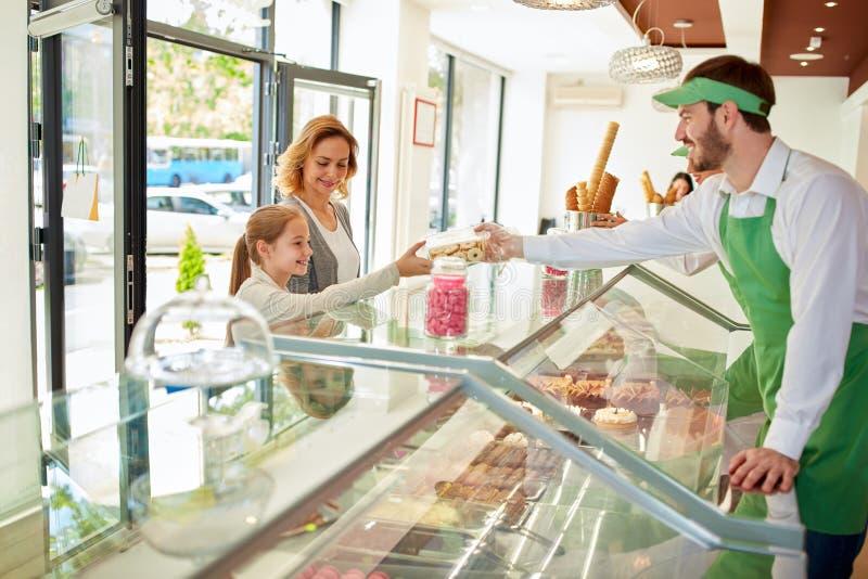Verkoper in de verkopende desserts van de banketbakkerijwinkel royalty-vrije stock afbeelding