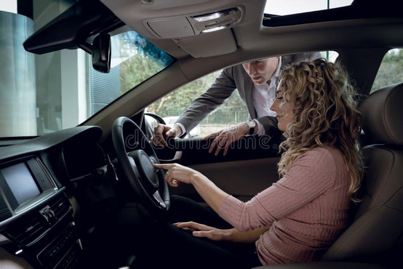 Verkoper die aan klantenzitting verklaren in auto royalty-vrije stock afbeeldingen